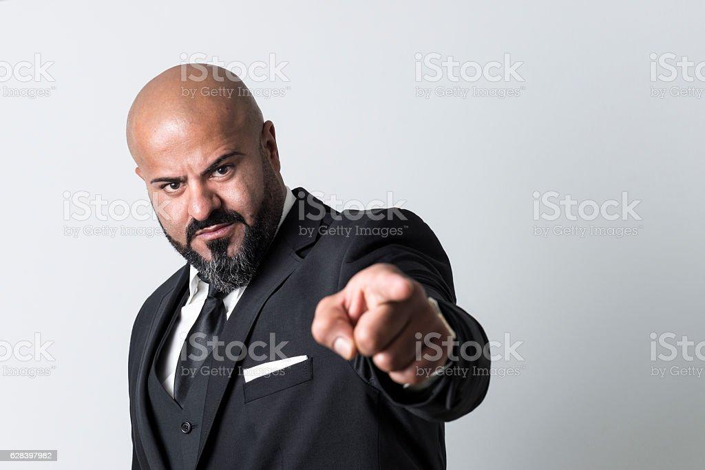 bald businessman with black beard pointing at camera stock photo