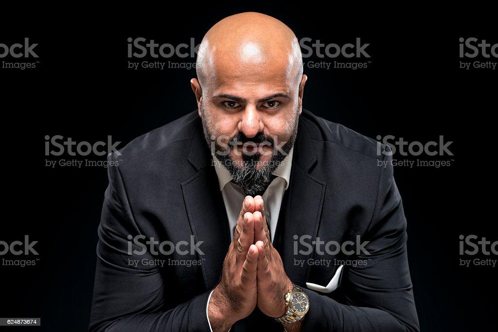 bald businessman with black beard praying stock photo