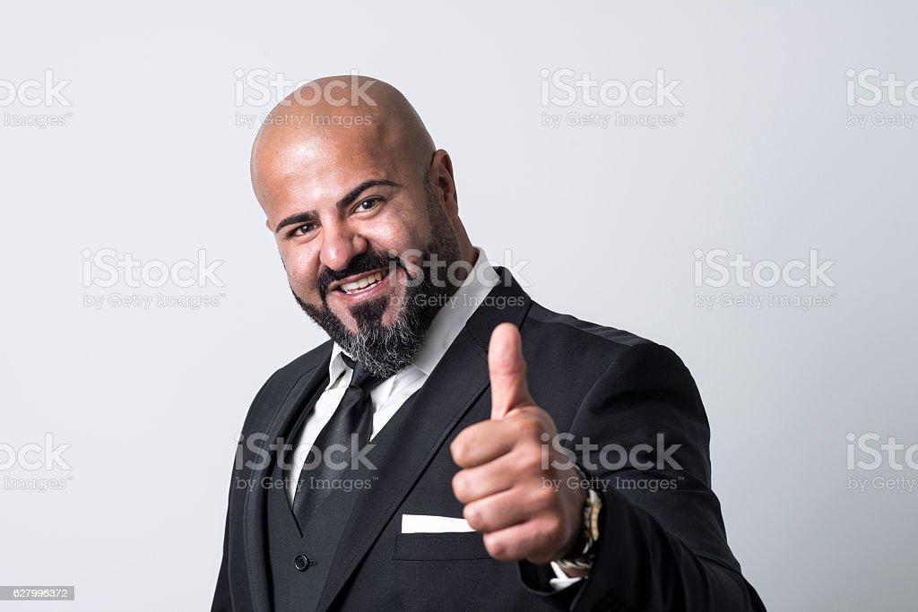 bald businessman with thumb up smiling at camera stock photo