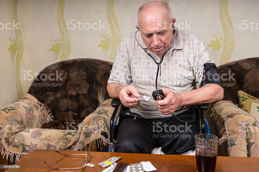 Bald Elderly Man with BP Apparatus and Medicines stock photo