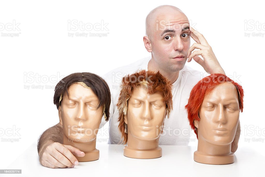 Bald guy choosing his new wig royalty-free stock photo