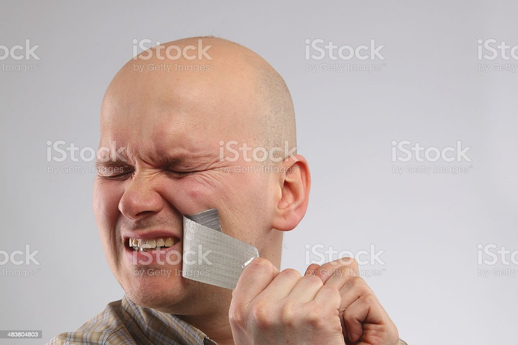 Bald guy is covering the tape on mouth stock photo