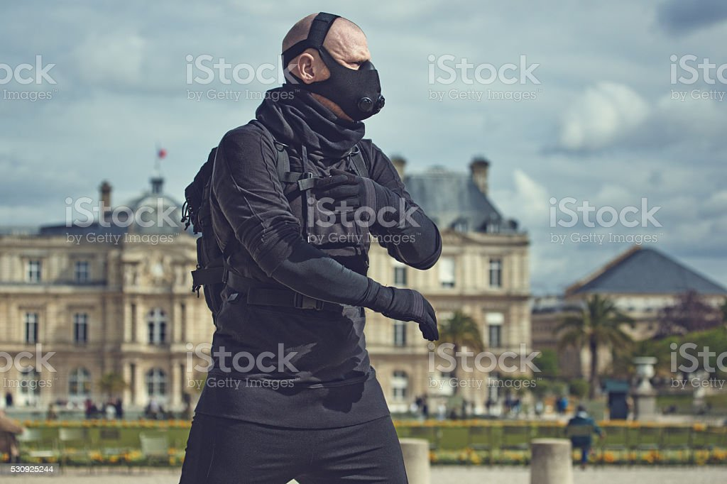 Bald male jogging in black in Paris wearing breathing apparatus stock photo