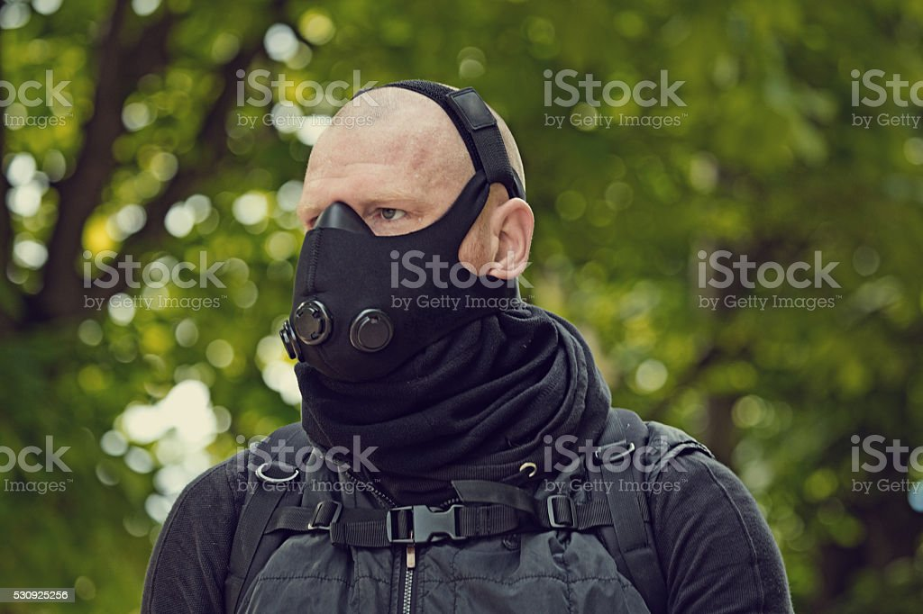 Bald male posing in black in park wearing breathing apparatus stock photo