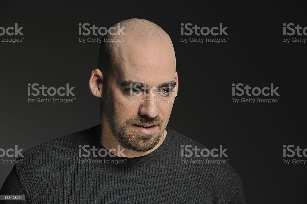 Bald man against black background stock photo
