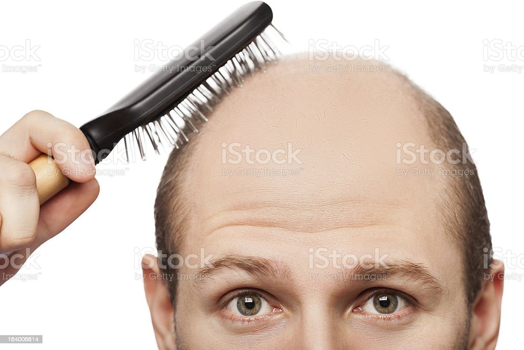 Bald man attempting to use hairbrush stock photo