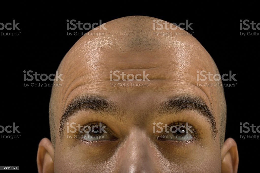 A bald man looking like he is thinking stock photo