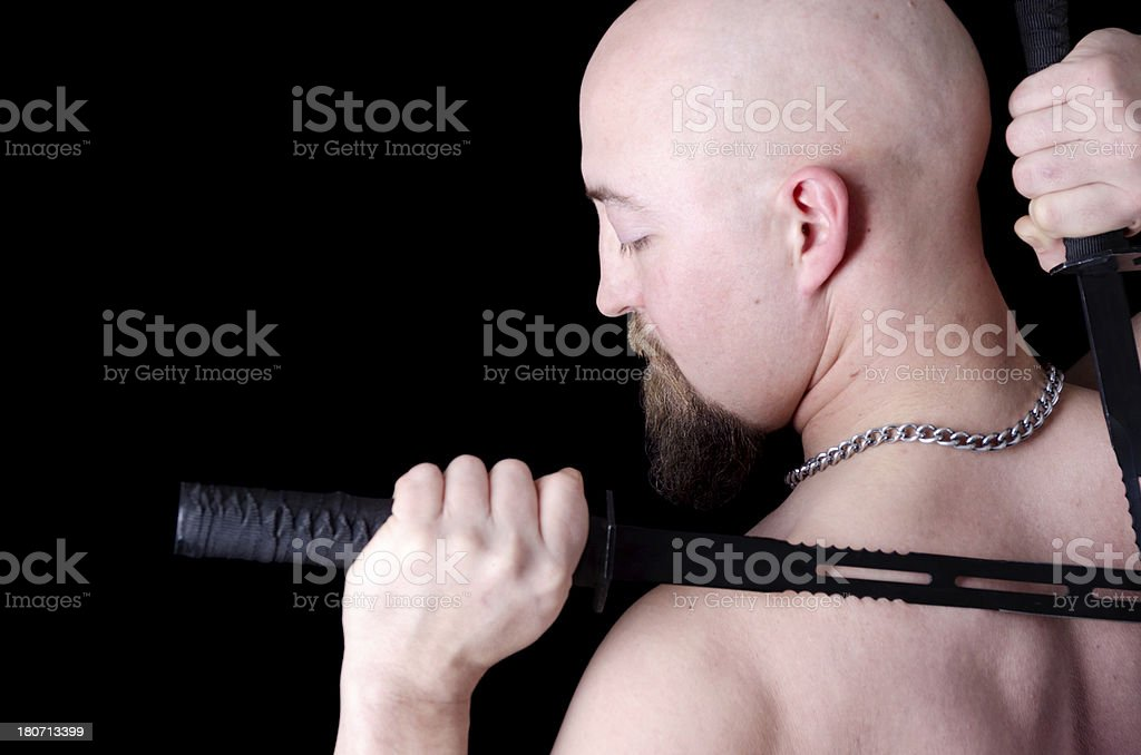 Bald man with dual swords over shoulders. royalty-free stock photo