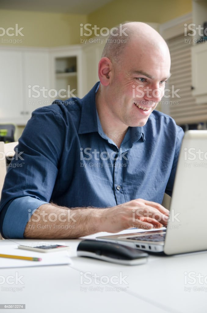 Bald man working on his laptop on dining room table stock photo