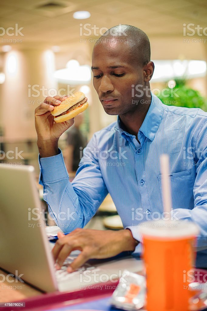 Bald office worker eating burger while typing on laptop stock photo