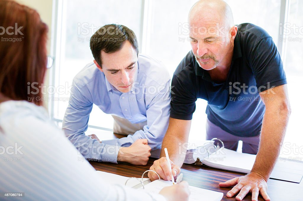Bald office worker explains policy to colleagues stock photo