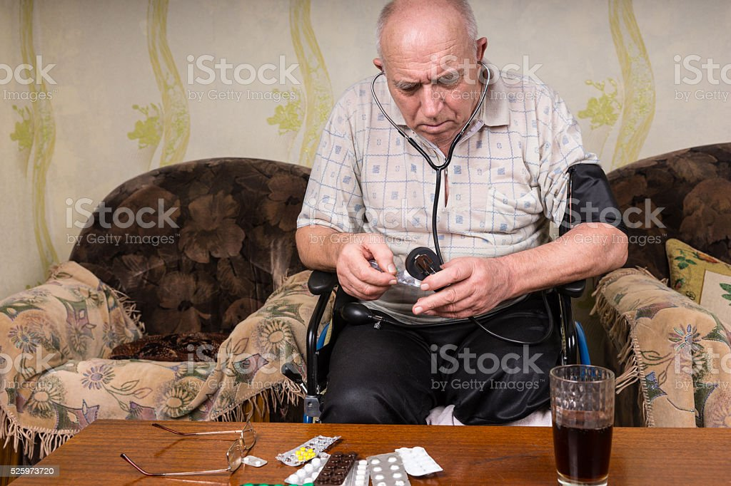 Bald Old Man Checking Medicines with BP Apparatus stock photo