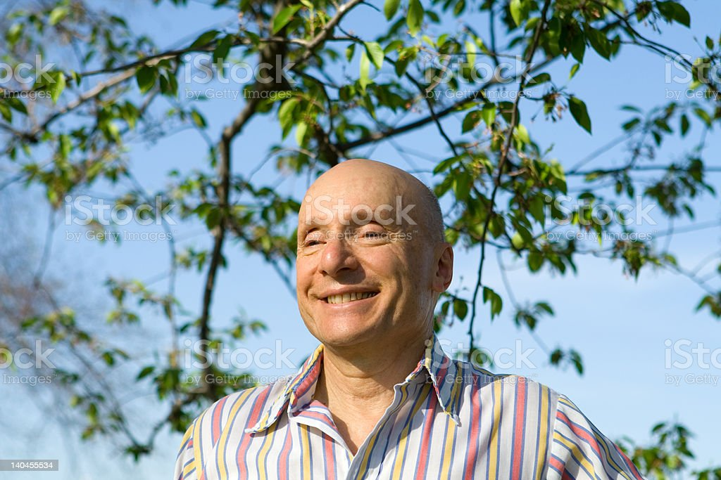 Bald White Senior Man Smiling Outside Tree Background royalty-free stock photo