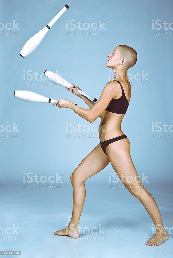 Bald-headed girl juggles royalty-free stock photo