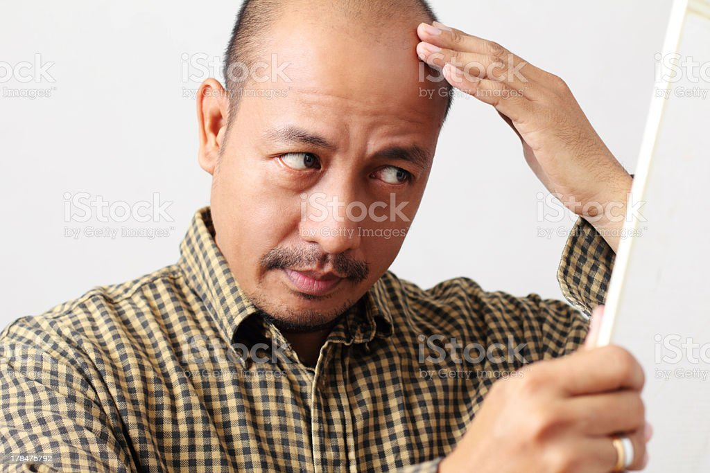 Balding man touching and looking at his head in the mirror stock photo