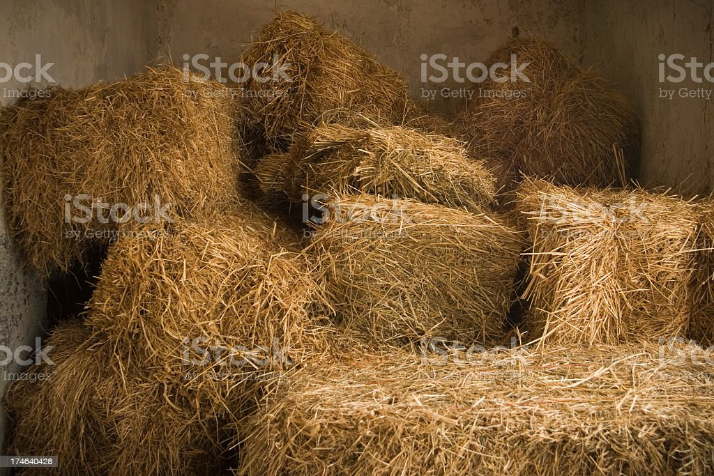 Bales of hay stacked in a pile inside a barn royalty-free stock photo