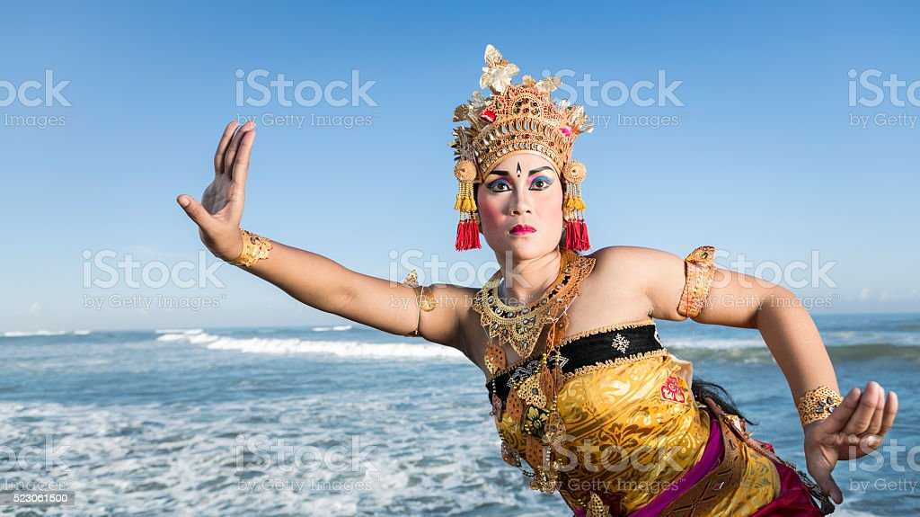 Bali female dancer in traditional costume by the blue sea stock photo