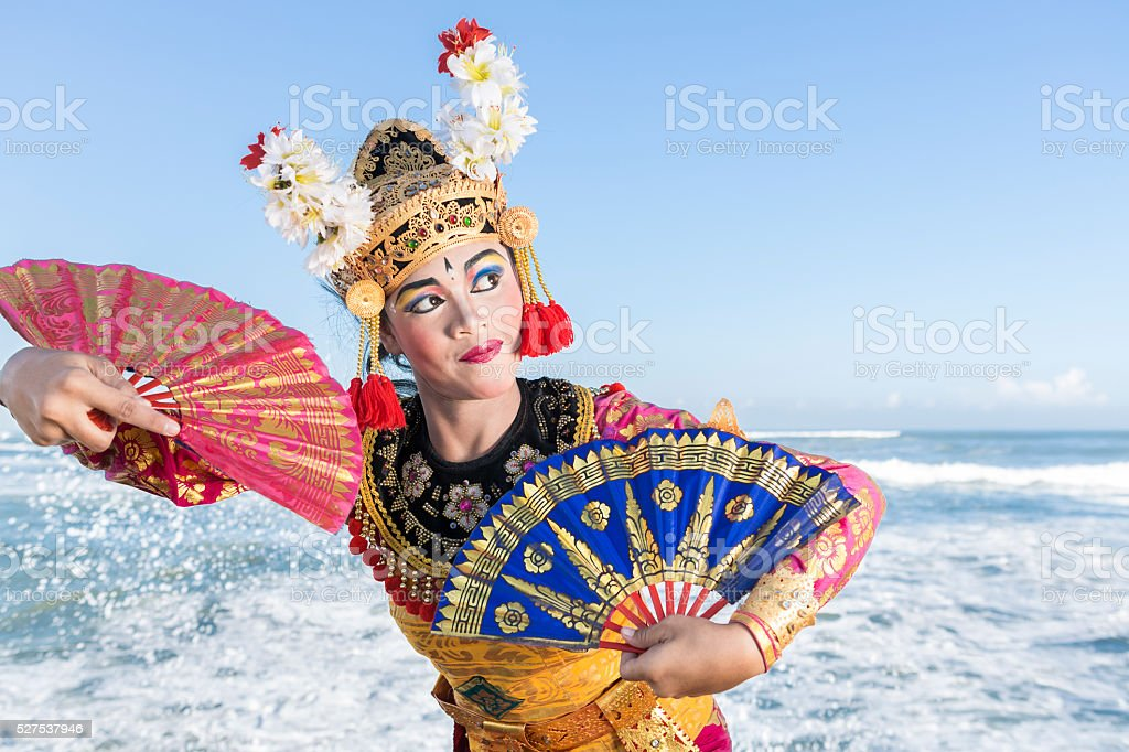 Bali female dancer in traditional costume playing with fans stock photo