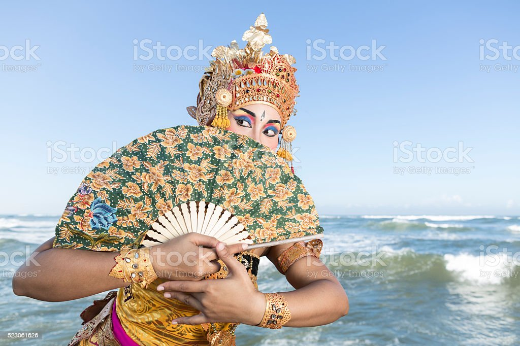 Bali female dancer in traditional costume with fan on beach stock photo