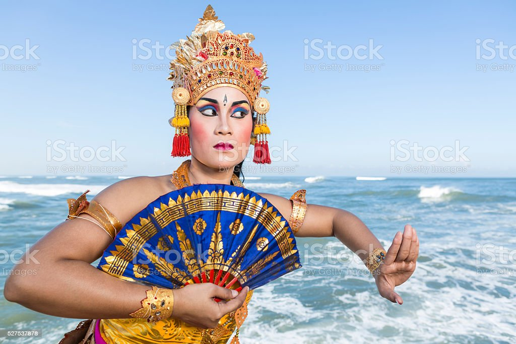 Bali female dancer in traditional costume with fan on coastline stock photo