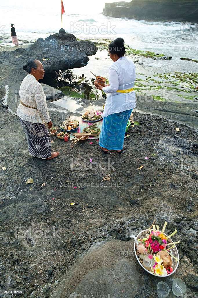 Balinese Hindu devotees pray at sunset. stock photo