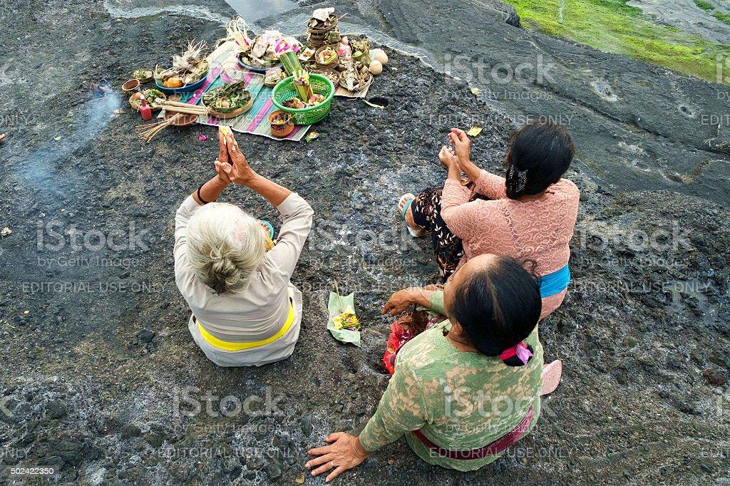 Balinese Hindu devotees pray during sunset. stock photo