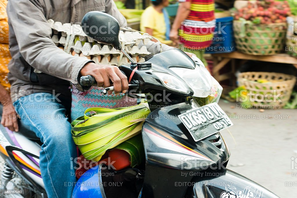 Balinese Man Driving Through Traditional Indonesian Street Market with Eggs stock photo