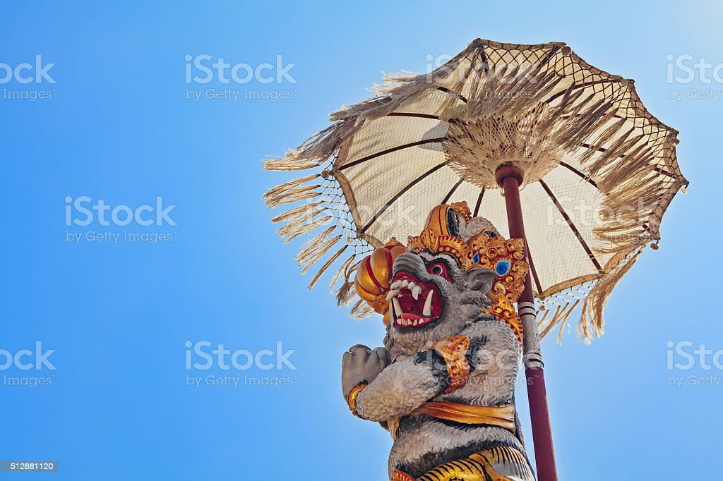Balinese monkey Hanuman under ceremonial umbrella in Bratan temple stock photo