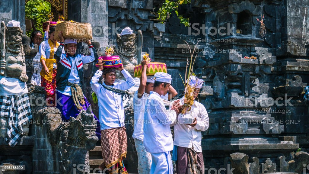 Balinese people in traditional clothes carry bless gift after ceremony at Pura Goa Lawah temple, Bali, Indonesia stock photo