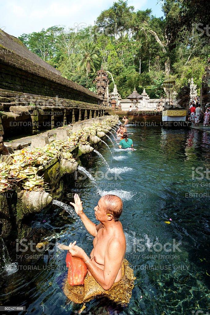 Balinese people praying at holy spring. stock photo