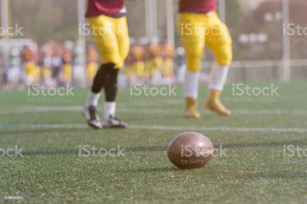 Ball and American football players on the field stock photo