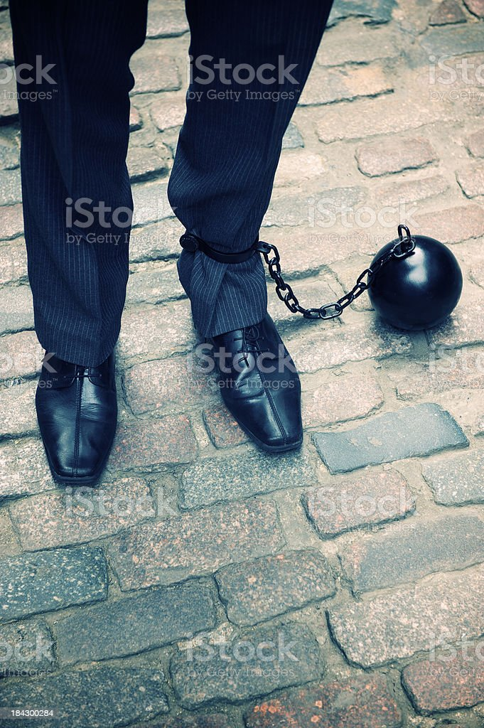 Ball and Chain Businessman Stands on Cobbled Street stock photo