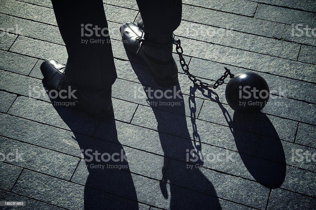 Ball and Chain Businessman with Long Shadows stock photo