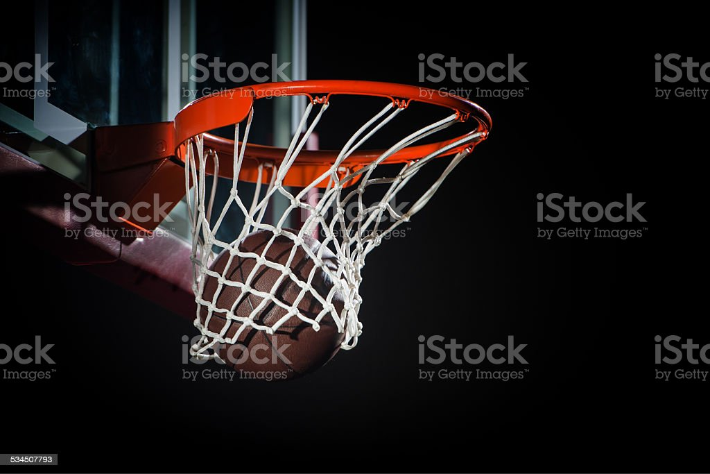 Ball falling through a Basketball Hoop stock photo