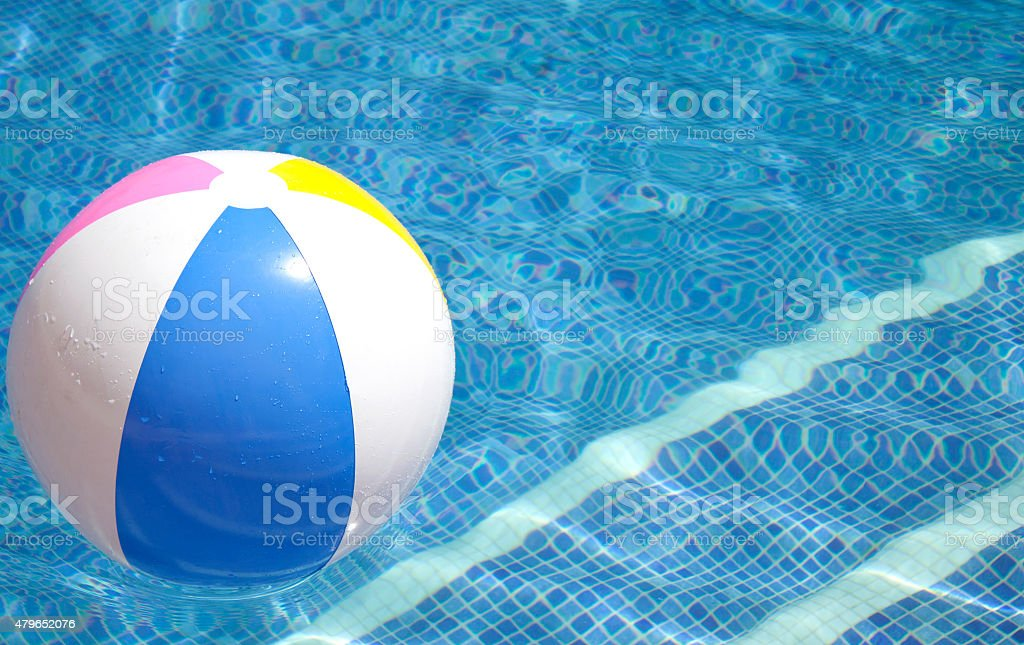 Ball floating in a blue swimming pool stock photo