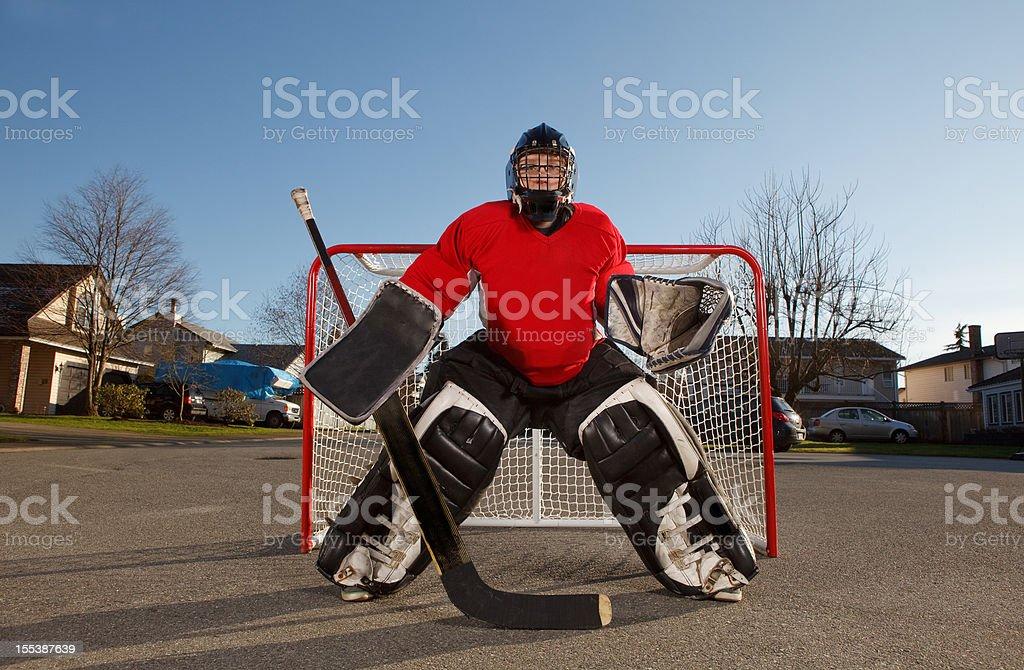 Ball hockey goalie in his net on a street stock photo