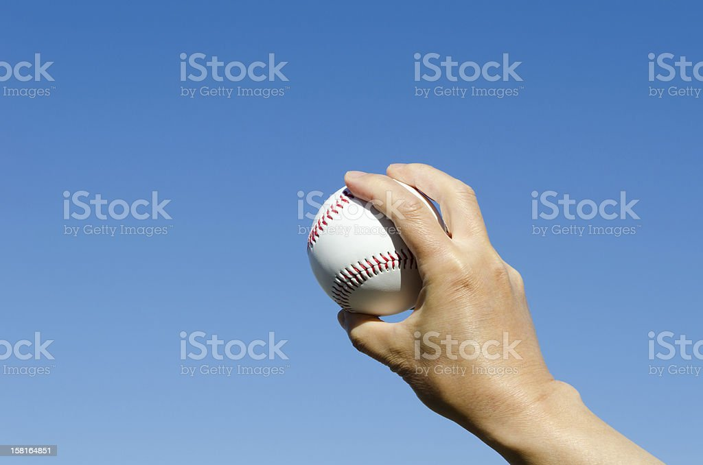 A ball in the hand against blue sky.