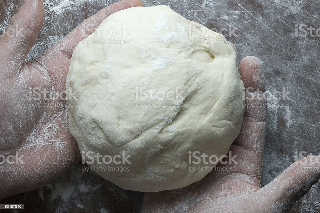 Ball of dough in baker's hands royalty-free stock photo