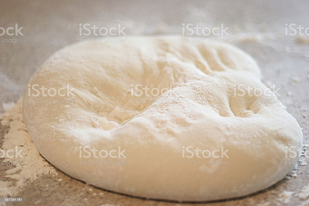 A ball of fresh made dough resting on a granite surface royalty-free stock photo
