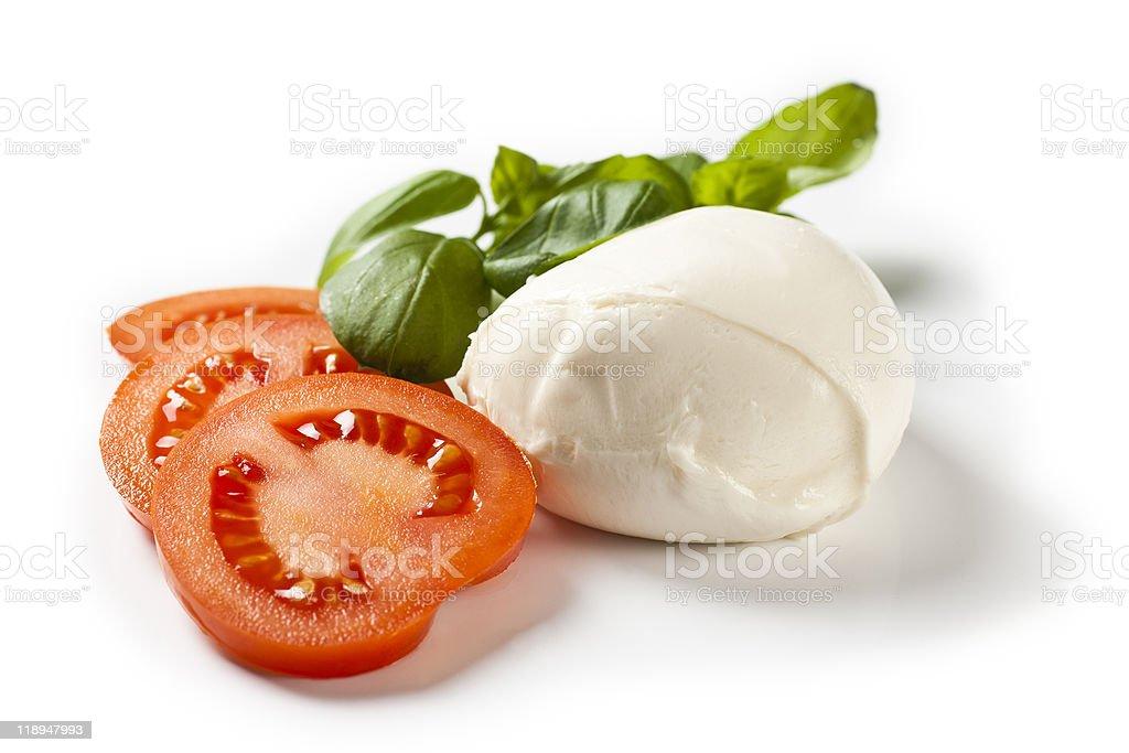 Ball of mozzarella cheese next to tomato slices and greens royalty-free stock photo