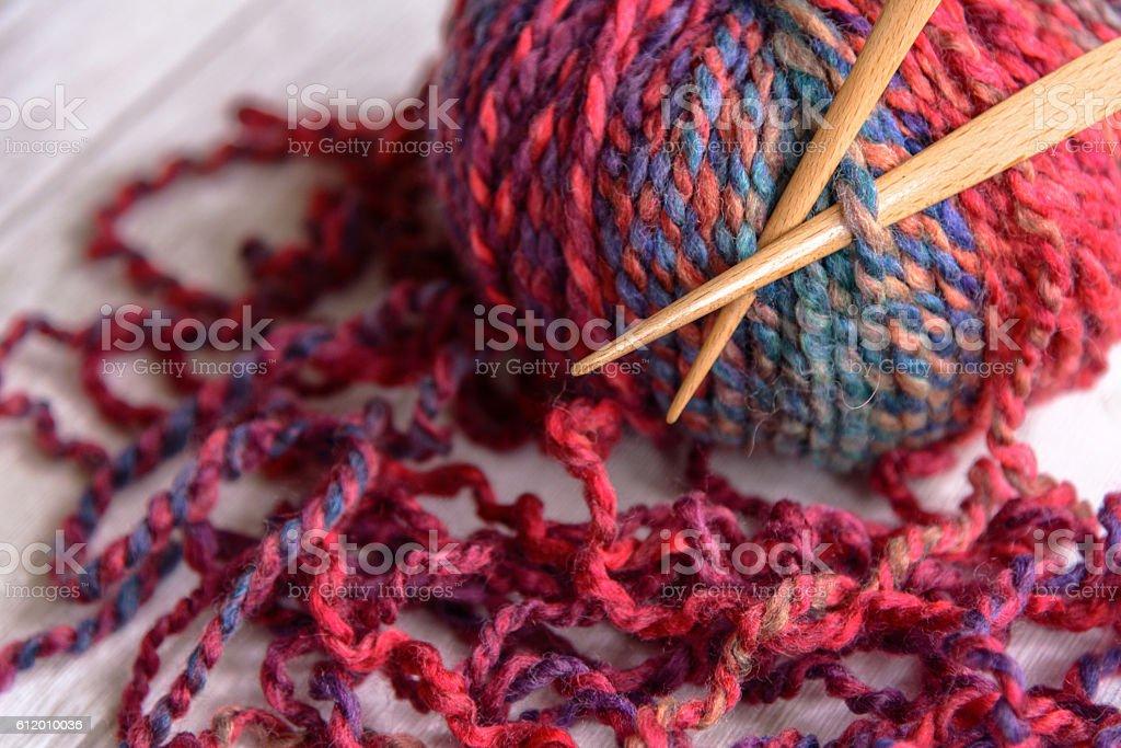 ball of purple yarn and knitting needles stock photo