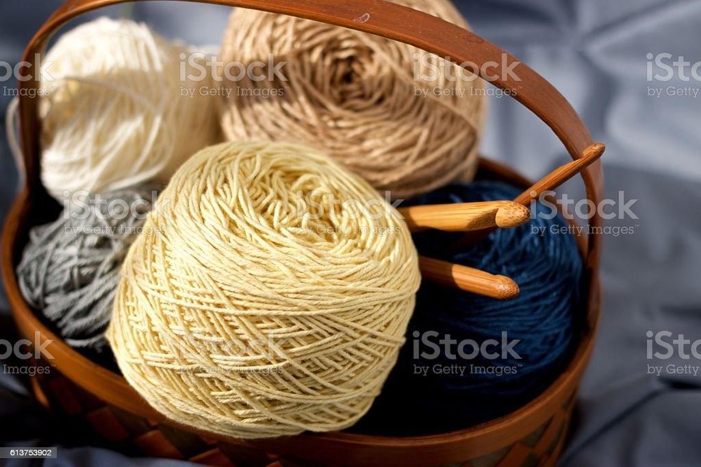 Ball of yarn beige tone in basket on fabric stock photo