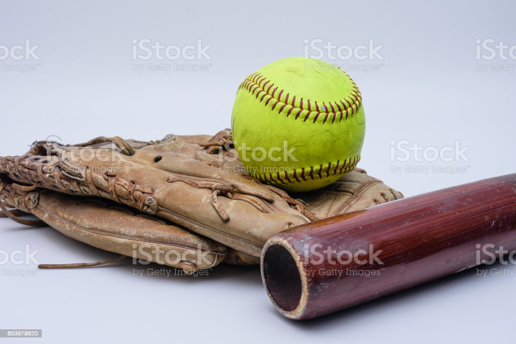 A ball sits on top of old glove with wood bat