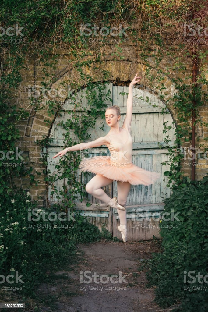 Ballerina dancing outdoors classic ballet poses in urban background stock photo