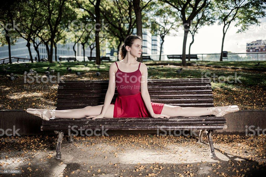 Ballerina doing a split on a park bench stock photo