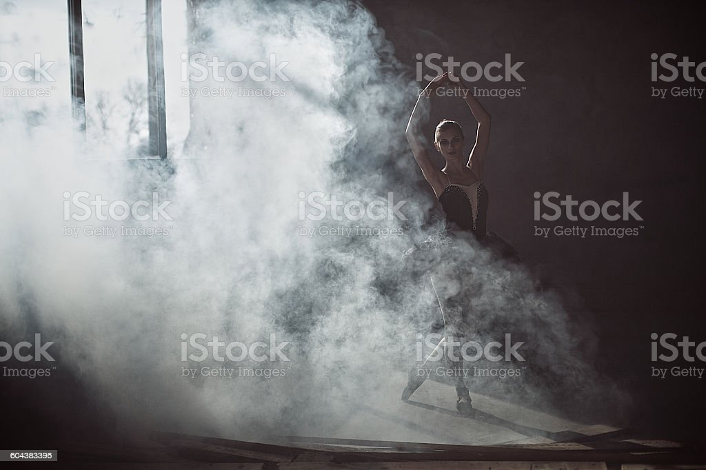 ballerina in a black dress surrounded by smoke stock photo