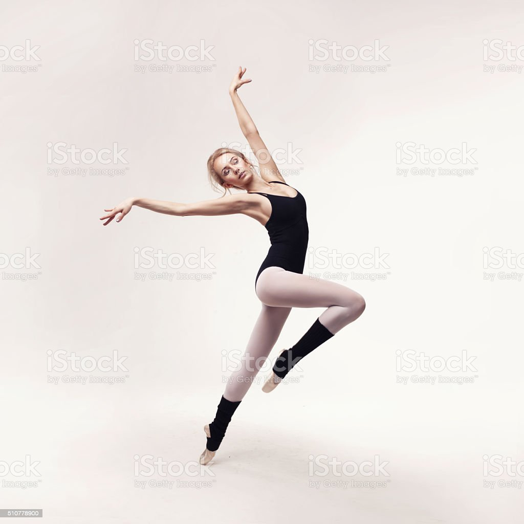 Ballerina in black outfit posing on toes stock photo