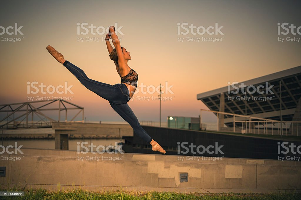 Ballerina jumping in the city stock photo
