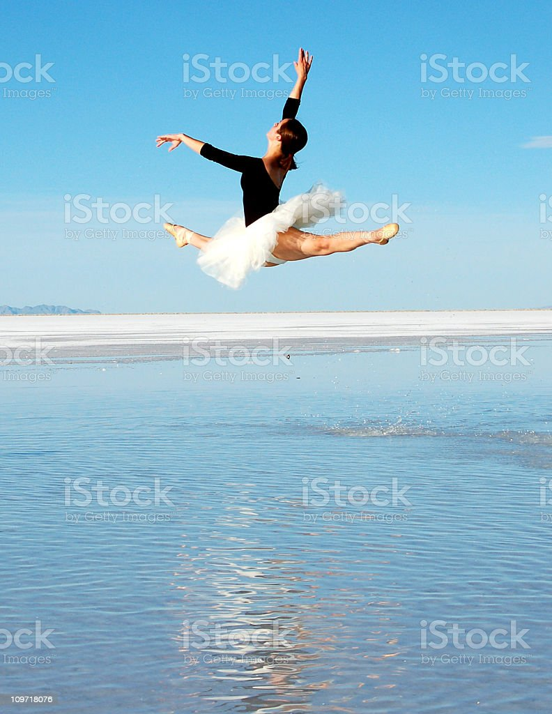 Ballerina Leaping Across Water on Salt Flats with Blue Sky stock photo