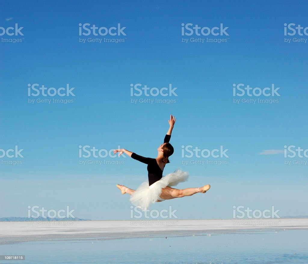 Ballerina leaping over water on the salt flats on a blue sky stock photo